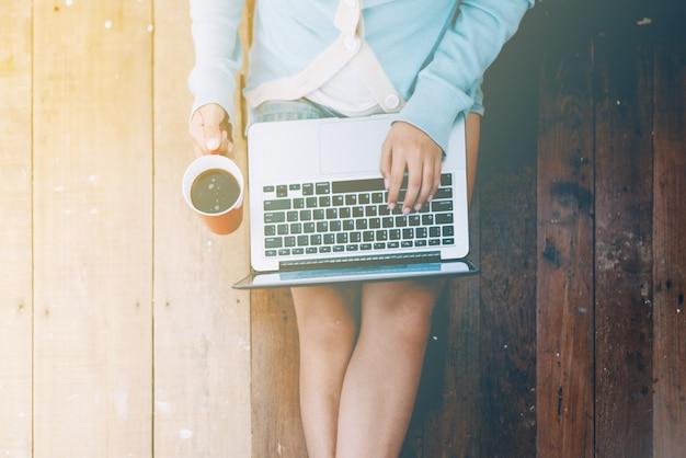 Het mooie meisje gebruikte laptop en koffiekop in de handen die van het meisje op een houten vloer zitten
