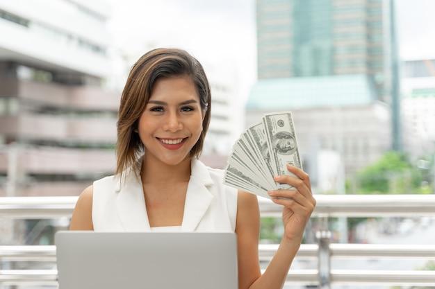Het mooie meisje glimlachen in bedrijfsvrouwenkleren gebruikend laptop computer en toont ter beschikking de rekeningen van de geldamerikaanse dollar