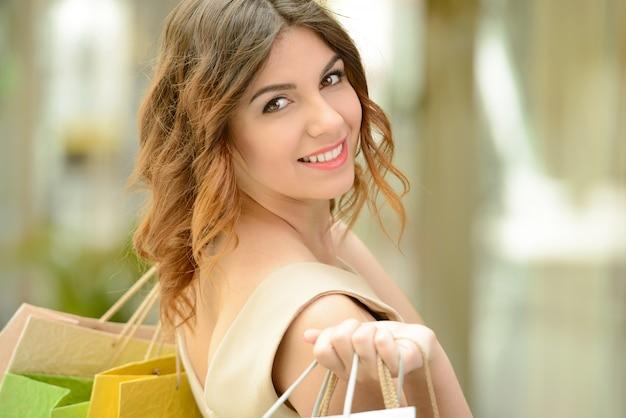 Het mooie meisje glimlacht en draagt zakken.