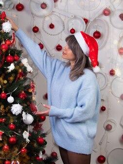 Het mooie meisje hangt kerstmisspeelgoed aan de boom