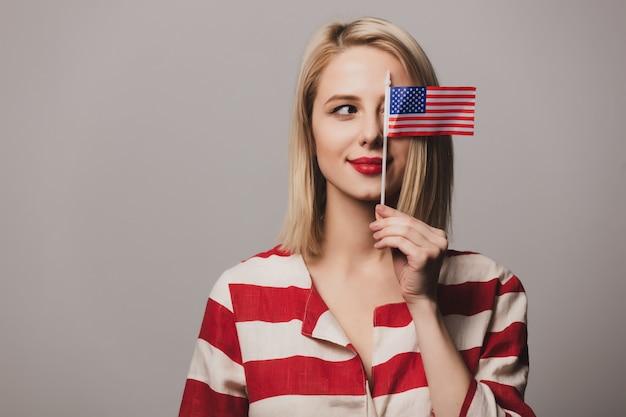 Het mooie meisje houdt de vlag van de verenigde staten van amerika