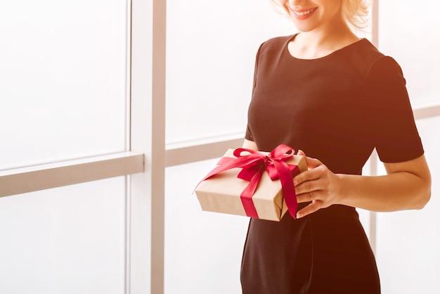 Het mooie meisje houdt een geschenk of een verrassing in de hand
