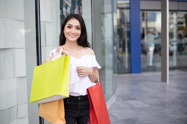 Het mooie meisje houdt het winkelen zakken en glimlacht terwijl het doen het winkelen in de supermarkt / het wandelgalerij