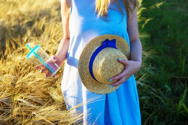 Het mooie meisje in blauwe kleding houdt een glas en een hoed in handen