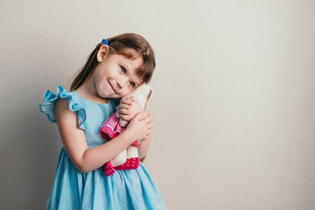 Het mooie meisje in blauwe kleding koestert haar stuk speelgoed konijn copyspace