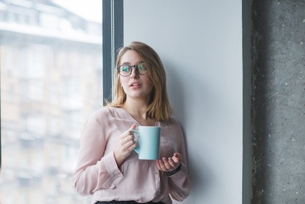 Het mooie meisje in de bril staat in de muur bij het raam met een kopje koffie.