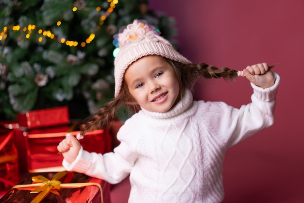 Het mooie meisje in de hoed die pret doet stelt dichtbij voor en kerstmisboom