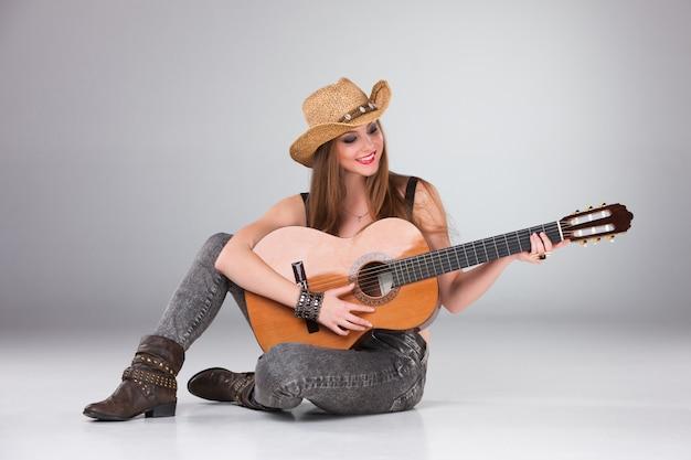 Het mooie meisje in een cowboyhoed en akoestische gitaar.