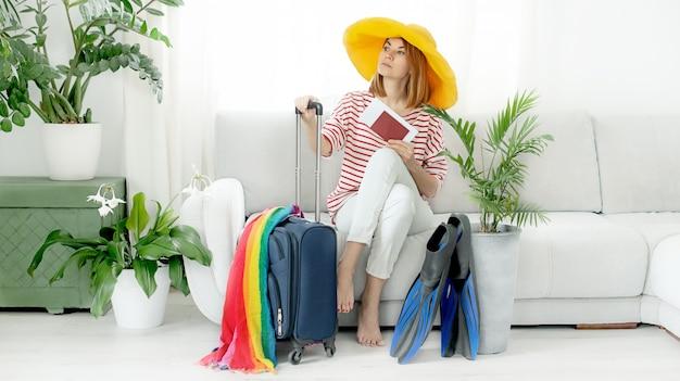 Het mooie meisje in een gele hoed blijft thuis en plant een reis op vakantie. koffer en flippers om te duiken.
