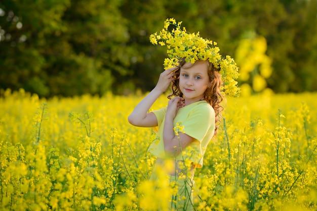 Het mooie meisje in een gele jurk op het bloeiende veld