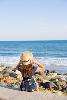 Het mooie meisje in een hoed zit dichtbij het overzees op stenen