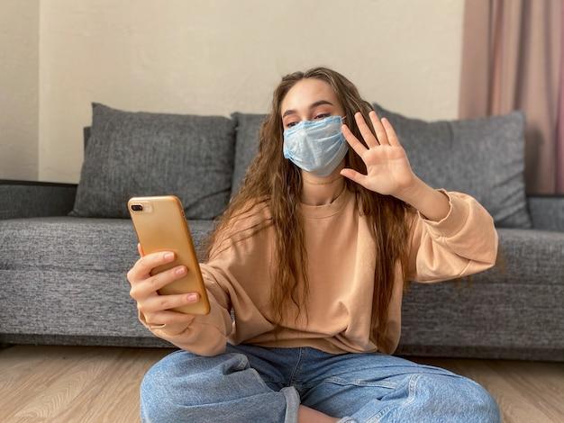 Het mooie meisje in een medisch masker met een smartphone in haar handen spreekt via videoverbinding met vrienden, verwanten