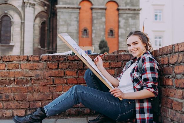 Het mooie meisje in een plaidoverhemd trekt oude gebouwen terwijl het zitten dichtbij een bakstenen muur.