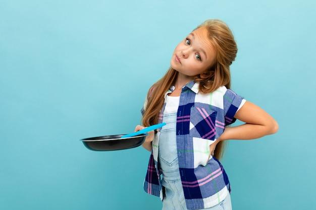 Het mooie meisje in een toevallig overhemd houdt een pan in zijn hand op lichtblauw