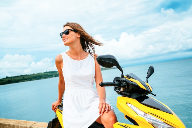 Het mooie meisje in een witte kleding zit op een autoped op blauwe overzeese achtergrond