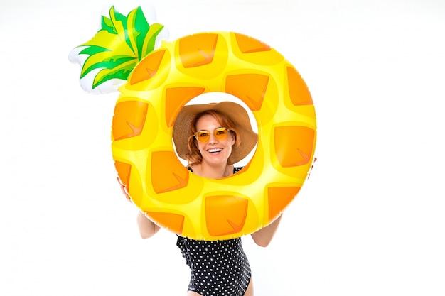 Het mooie meisje in glazen en een strohoed houdt een ananasvormige zwemmende ring op een witte muur