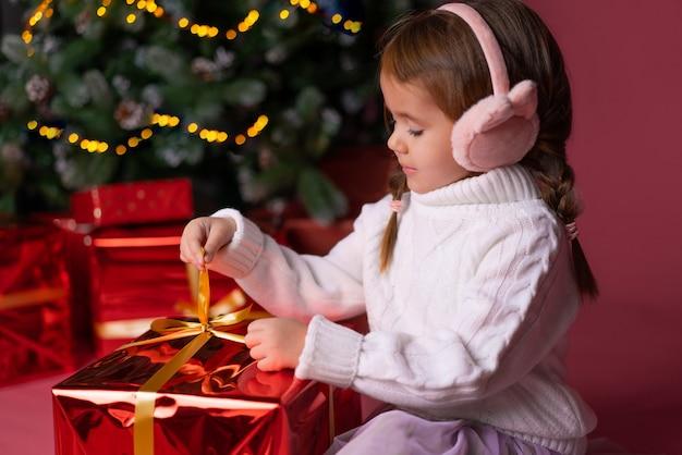 Het mooie meisje in hoed het openen stelt dichtbij kerstmisboom voor