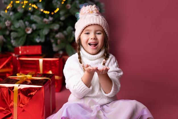 Het mooie meisje in hoed het spelen met sneeuw dichtbij stelt en kerstmisboom voor