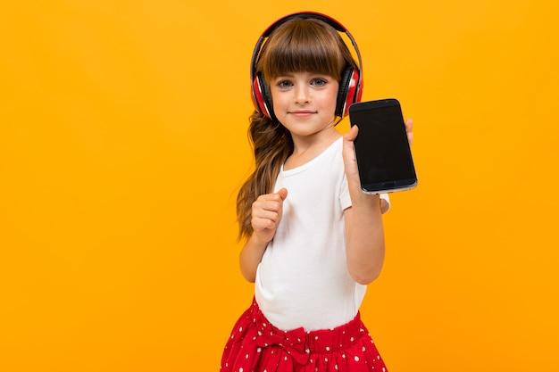 Het mooie meisje in kleding luistert aan muziek die op geel of oranje wordt geïsoleerd