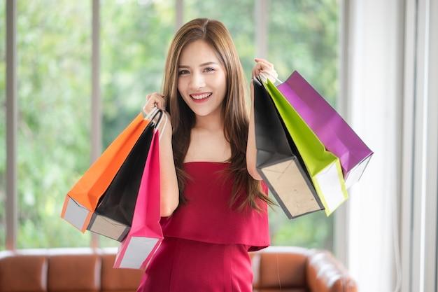 Het mooie meisje in rode jurk houdt van winkelen. ze heeft veel tassen en koopt ze van su