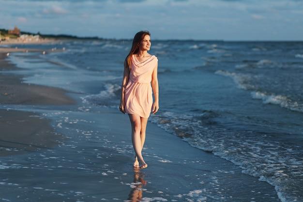 Het mooie meisje in roze kleding wandelt langs de kust in de avond