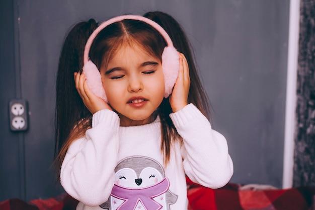 Het mooie meisje in roze pluizige hoofdtelefoons zit met gesloten ogen op grijs.