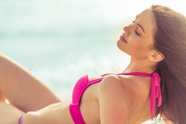 Het mooie meisje in roze zwempak ligt met gesloten ogen.