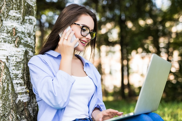 Het mooie meisje in spijkerbroek werkt met laptop in stadspark dat met telefoon spreekt