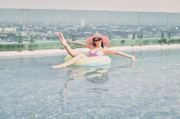 Het mooie meisje in swimwear ontspant bij het zwembad.