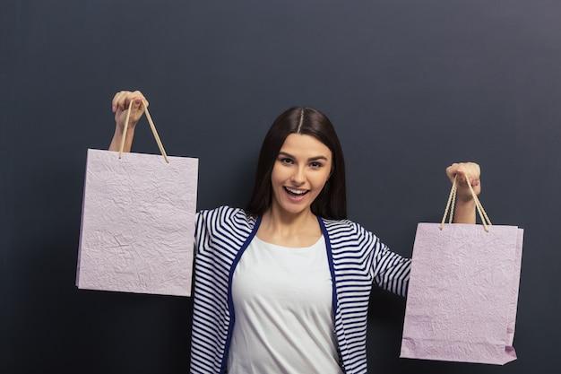Het mooie meisje in vrijetijdskleding houdt boodschappentassen.