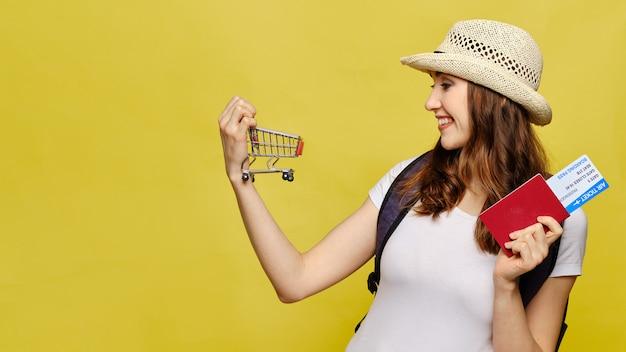 Het mooie meisje in vrijetijdskleding met een paspoort en kaartjes houdt een kar als concept reisverkoop.