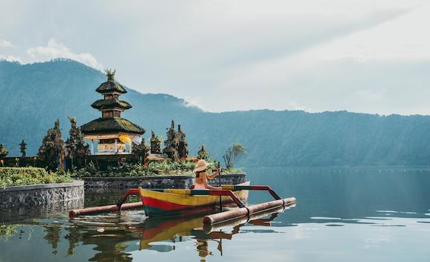 Het mooie meisje kayaking op de catamaran bij de bratan tempel van ulundatu pura, in bali