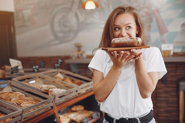 Het mooie meisje koopt broodjes bij de bakkerij