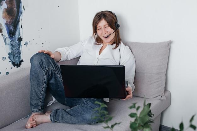 Het mooie meisje ligt thuis op de bank met een laptop in haar handen en koptelefoon, met positieve emoties en een mooie glimlach