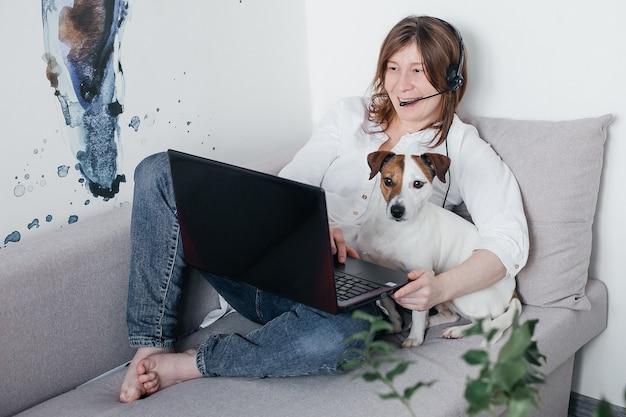 Het mooie meisje ligt thuis op de bank met een laptop in haar handen, naast een jack russell-hond