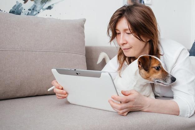 Het mooie meisje ligt thuis op de bank met een tablet in haar handen, naast een jack russell-hond