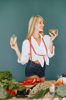 Het mooie meisje maakt een salade. sportieve blondine in een keuken. vrouw kiest tussen hamburger en salade.