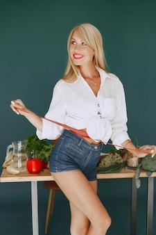 Het mooie meisje maakt een salade. sportieve blondine in een keuken. vrouw meet haar taille.