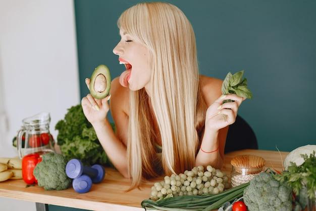 Het mooie meisje maakt een salade. sportieve blondine in een keuken. vrouw met avocado.