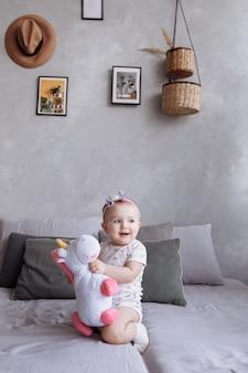 Het mooie meisje met een hoepel speelt thuis met stuk speelgoed eenhoorn op bed. concept van kinderdag. gelukkige baby's, familiedag