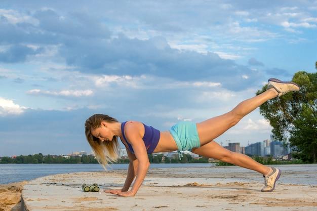 Het mooie meisje met een sportfiguur doet fitness buitenshuis in de buurt van het meer.