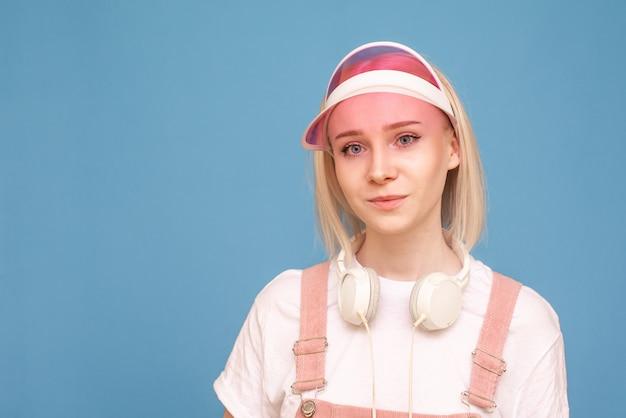 Het mooie meisje met hoofdtelefoons en een roze glb is op een blauwe achtergrond en bekijkt de camera, een dicht portret