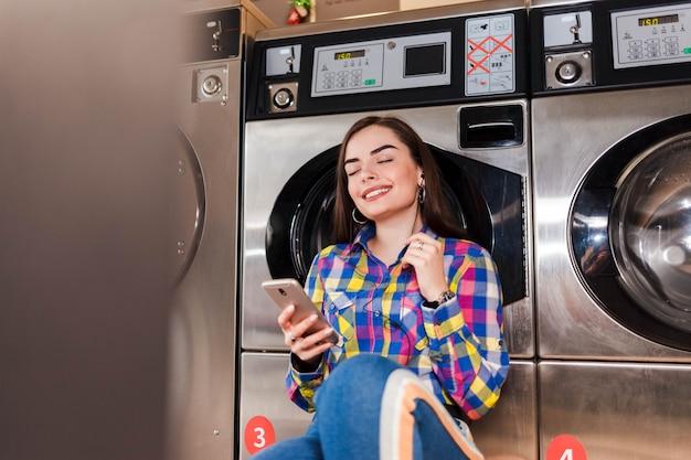 Het mooie meisje met in hand smartphone luistert aan muziek die op een wasmachine in openbare wasserij leunen