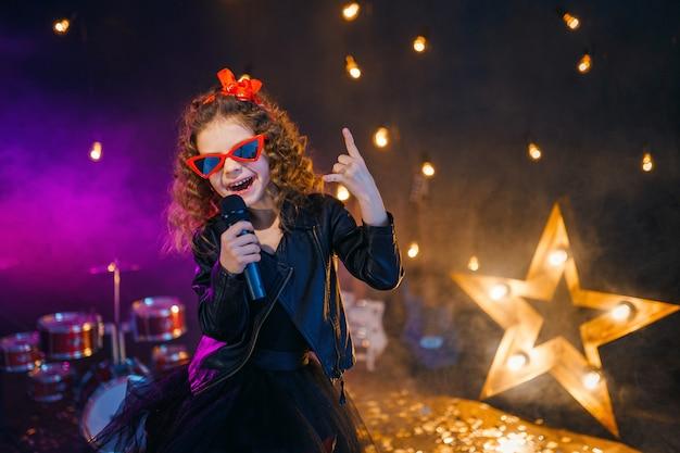 Het mooie meisje met krullend haar dat leerjasje en rode zonnebril draagt zingt in een draadloze microfoon voor karaoke in opnamestudio