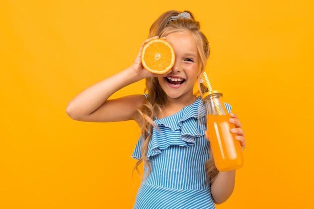Het mooie meisje met lang haar drinkt sap en glimlacht, beeld dat op gele achtergrond wordt geïsoleerd