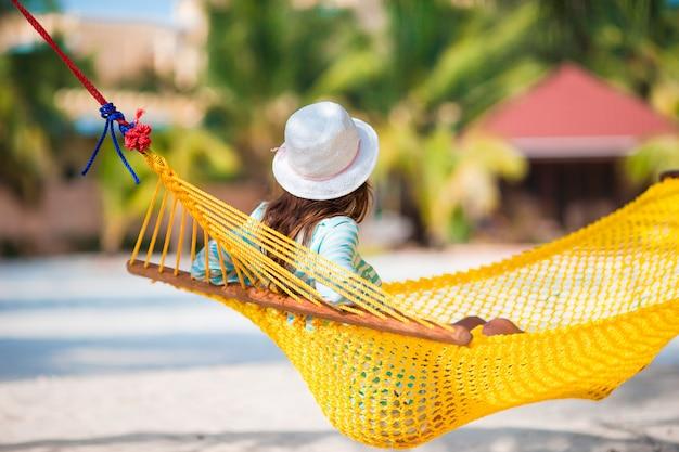 Het mooie meisje ontspannen bij hangmat op wit strand
