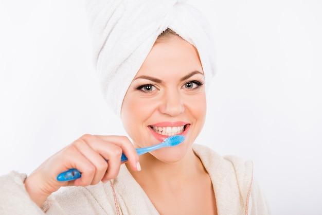 Het mooie meisje poetst haar tanden op een witte achtergrond