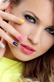 Het mooie meisje raakt haar gezicht met gekleurde vingers