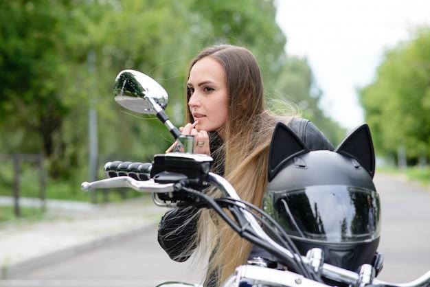 Het mooie meisje schildert haar lippen op een motorfiets.