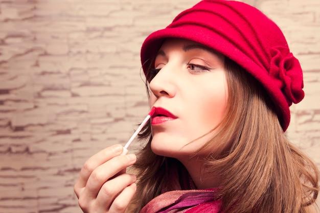 Het mooie meisje schildert haar lippen